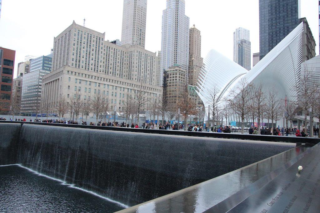"""Einer der beiden Brunnen des 09/11 Memorial. Im Hintergrund der Bahnhof """"The Oculus"""""""